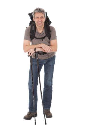 Starszy mężczyzna z plecakiem i wędrówki biegunów. Samodzielnie na białym tle