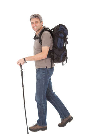 trekking pole: Senior man with backpack and hiking poles. Isolated on white