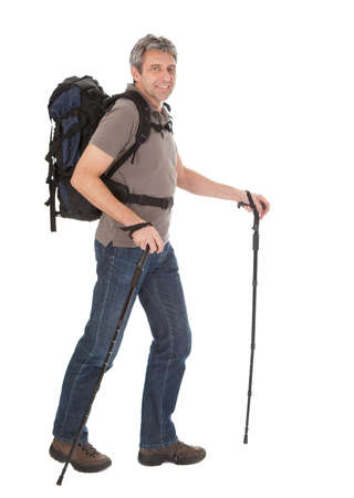 Senior man with backpack and hiking poles. Isolated on white photo