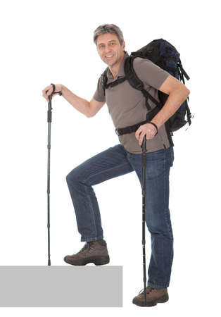 upstairs: Senior man with backpack and hiking poles. Isolated on white