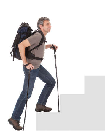upstairs: Senior man with backpack and hiking poles climbing a staircase. Isolated on white