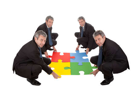 Senior business people assembling a jigsaw puzzle. Teamwork concept. Isolated in white photo