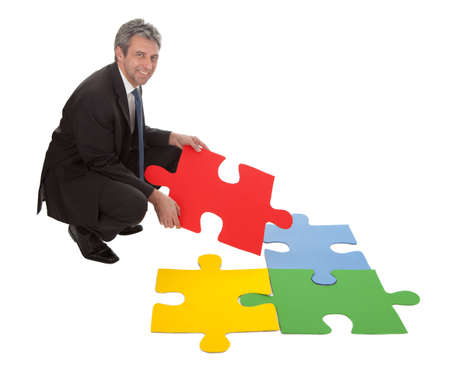 Senior businessman assembling a jigsaw puzzle. Isolated in white photo
