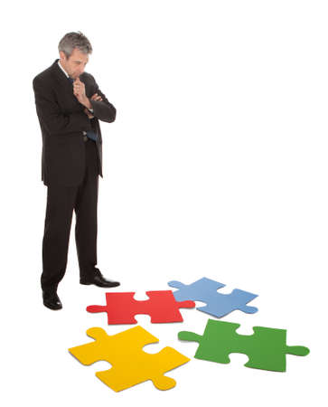 assembling: Senior businessman assembling a jigsaw puzzle. Isolated in white