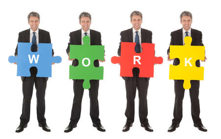 Group of business people holding jigsaw puzzle. Isolated on white Stock Photo - 12983534