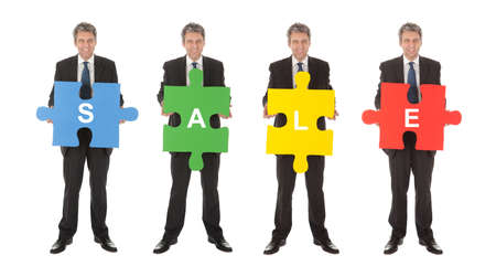 Group of business people holding jigsaw puzzle. Isolated on white photo