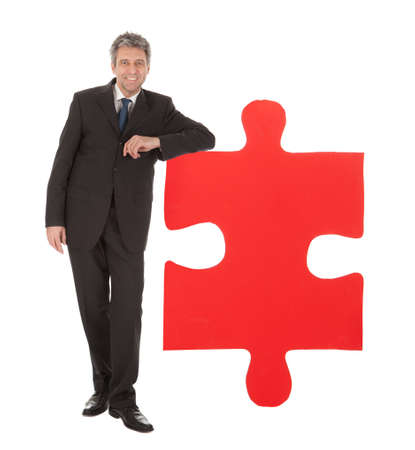 Senior businessman holding a jigsaw puzzle. Isolated in white Stock Photo - 12983497