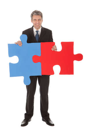 Senior businessman holding a jigsaw puzzle. Isolated in white photo