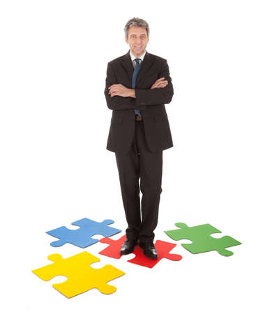 Senior businessman standing on a jigsaw puzzle. Isolated in white photo
