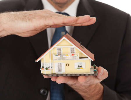 architectural styles: Businessman holding model of a house in his hands. Real-estate insurance concept