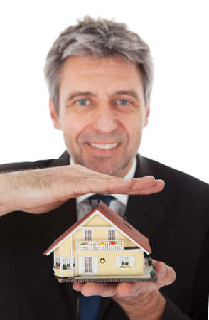 hands holding house: Businessman holding model of a house in his hands. Real-estate insurance concept