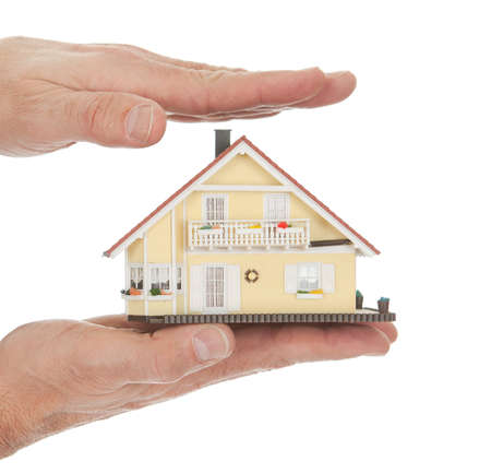Businessman holding model of a house in his hands. Real-estate insurance concept photo