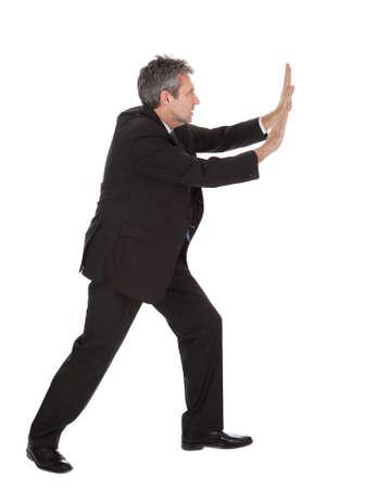 pushing: Portret van zakenman duwen kopie-ruimte. Geà ¯ soleerd op wit