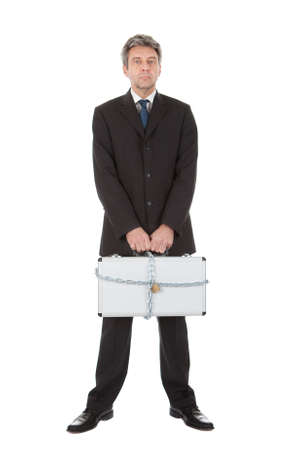 Businessman holding metal suitcase with chain and lock. Isolated on white Stock Photo - 12983459