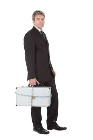 Businessman holding metal suitcase with chain and lock. Isolated on white Stock Photo - 12983455