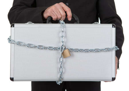 Businessman holding metal suitcase with chain and lock. Isolated on white photo