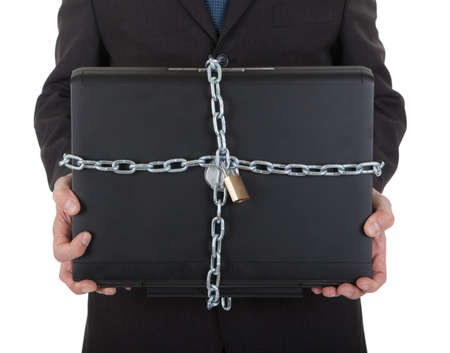 Businessman holding laptop with chain and lock. Isolated on white photo