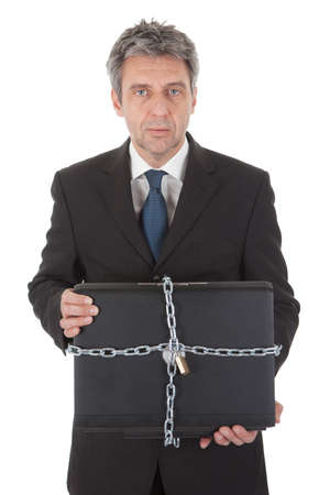 Businessman holding laptop with chain and lock. Isolated on white Stock Photo - 12983554