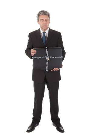 Businessman holding laptop with chain and lock. Isolated on white Stock Photo - 12983470