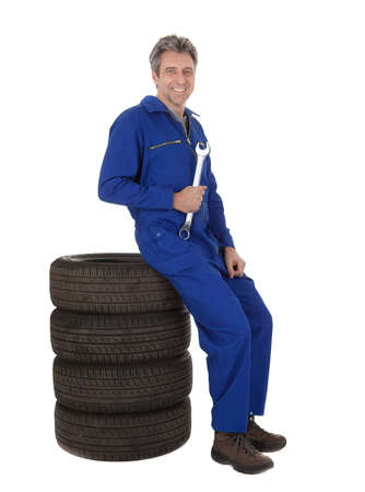 Automechanic sitting on car tires. Isolated on white photo