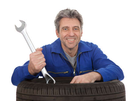Automechanic leaning on car tires. Isolated on white Stock Photo - 12983538