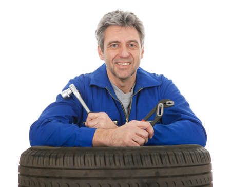 Automechanic leaning on car tires. Isolated on white photo