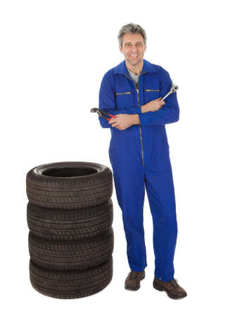 Automechanic standing next to car tires. Isolated on white Stock Photo - 12983490