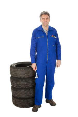 salopette: Automechanic debout � c�t� de pneus de voiture. Isol� sur fond blanc