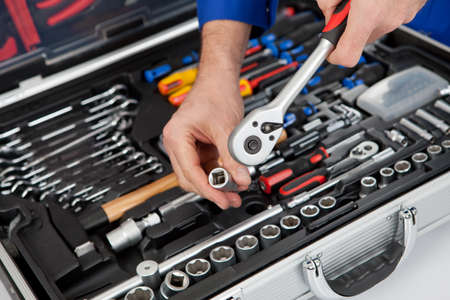 toolbox: Portrait of automechanic taking a wrench out of toolbox. Isolated on white Stock Photo