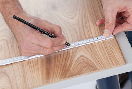 Worker drawing a mark on laminate using ruler photo