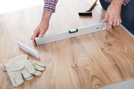 leveling: Worker measuring leveling of a laminate floor
