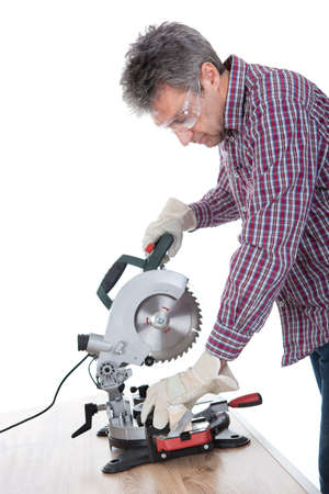 Worker cutting timber using circular electric saw photo