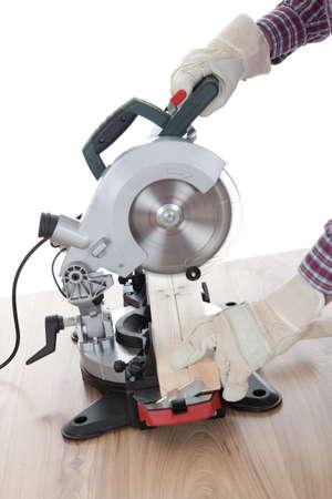 Worker cutting timber using circular electric saw photo