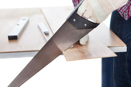 Worker cutting piece of laminate using hand saw photo