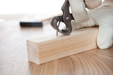 Close-up of worker pulling a nail from a plank photo
