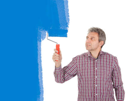 Senior adult painting wall in blue using a roller photo