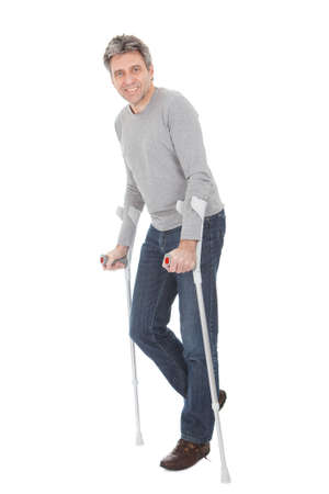 Senior man walking using crutches. Isolated on white photo