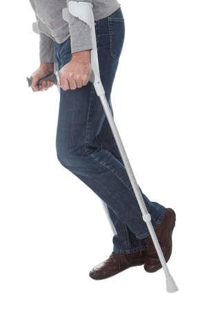 pierna rota: Hombre mayor caminando con muletas. Aislado en blanco