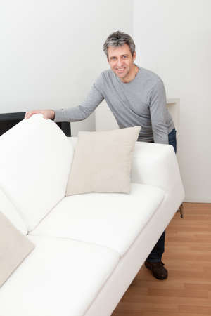 service lift: Senior man moving sofa at his home Stock Photo