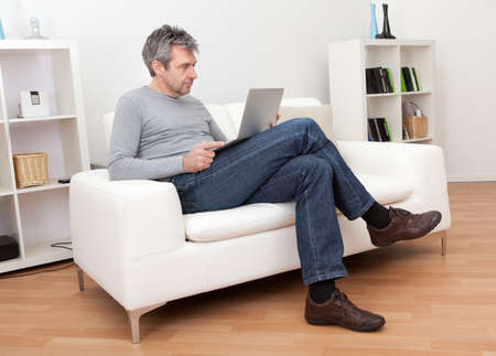 Senior man sitting in sofa at home and using laptop Фото со стока