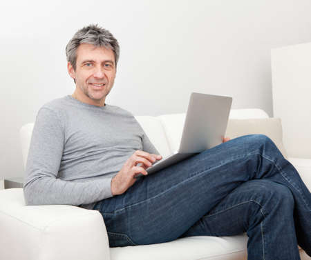 Senior man sitting in sofa at home and using laptop photo