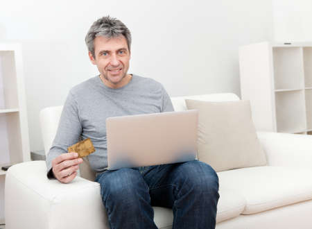 Senior man sitting in sofa and shopping online using laptop photo