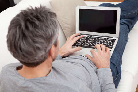 Senior man sitting in sofa at home and using laptop Stock Photo