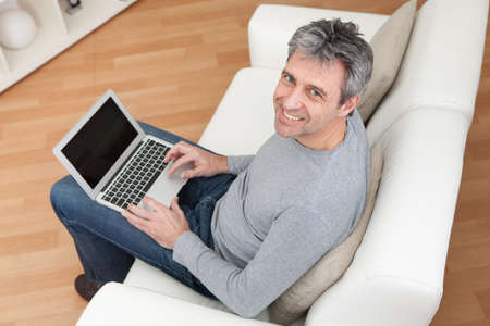 topdown: Senior man sitting in sofa at home and using laptop Stock Photo