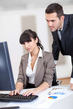 Manager overseeing business woman working on computer at the office Stock Photo - 13020793