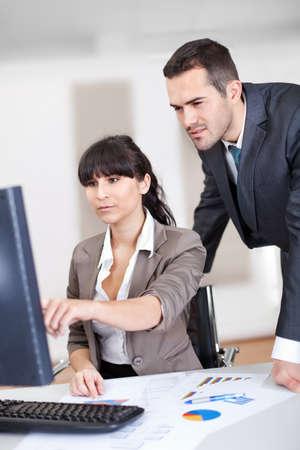 la gente de trabajo: Gerente de negocios de la supervisi�n de mujer que trabaja en la computadora en la oficina Foto de archivo