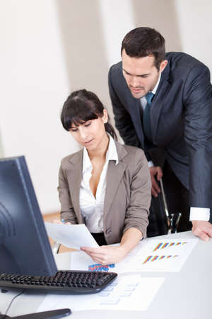 Manager overseeing business woman working on computer at the office Stock Photo - 13020753