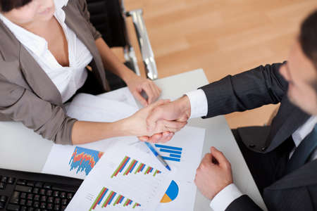 Two business people in the office at the meeting. Close-up on handshake Stock Photo - 13020502