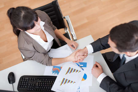 Two business people in the office at the meeting shaking hands photo