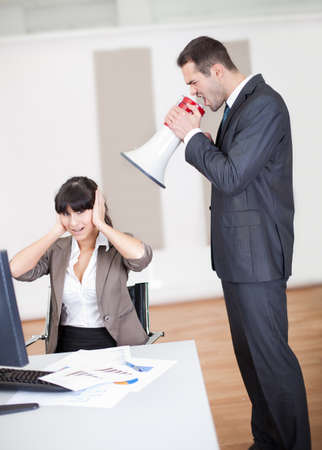 Angry businessman screaming at employee at the office in megaphone photo